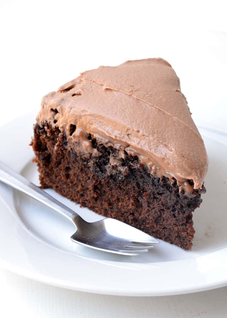A slice of chocolate mud cake on a white plate