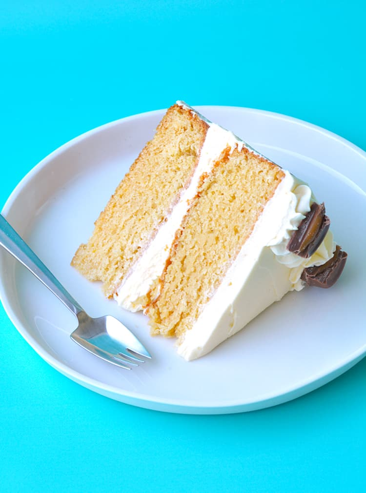 A slice of caramel mud cake on a white plate with a blue background.