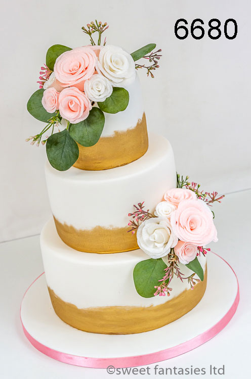 white wedding cake with roses & gold trim