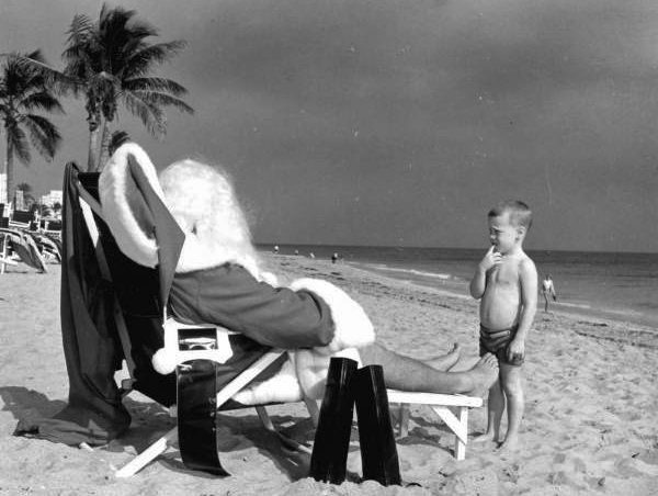 Child Looking at Santa relaxing at the beach circa 1964