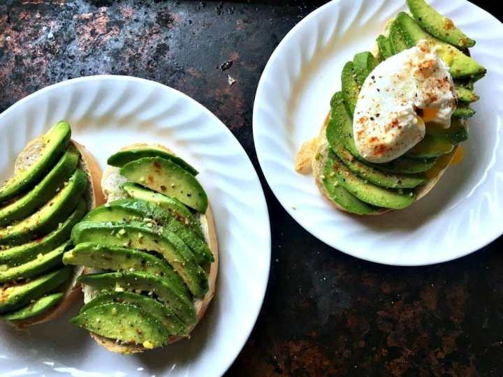 overhead shot of three avocado toasts, one plate with an avocado toast with poached egg on top and the others with sliced avocado only