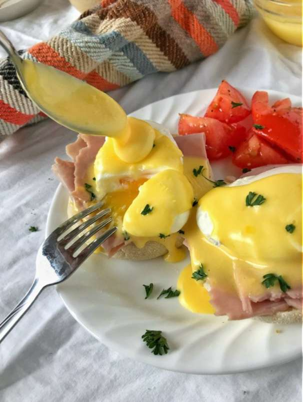 Close up of Eggs Benedict with poached egg cut, yolk running down onto ham, and a spoonful of Hollandaise being poured onto the egg.