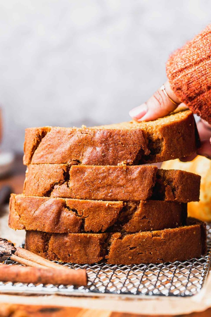a hand lifts a thick slice of spiced homemade pumpkin bread off a stack of them