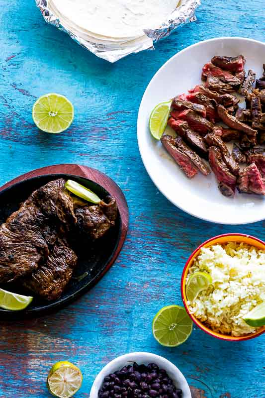authentic mexican carne asada prepared for tacos with rice, limes slices, and tortillas