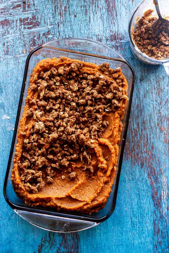 Overhead shot of unbaked sweet potato casserole with brown sugar topping in bowl and on the sweet potato filling