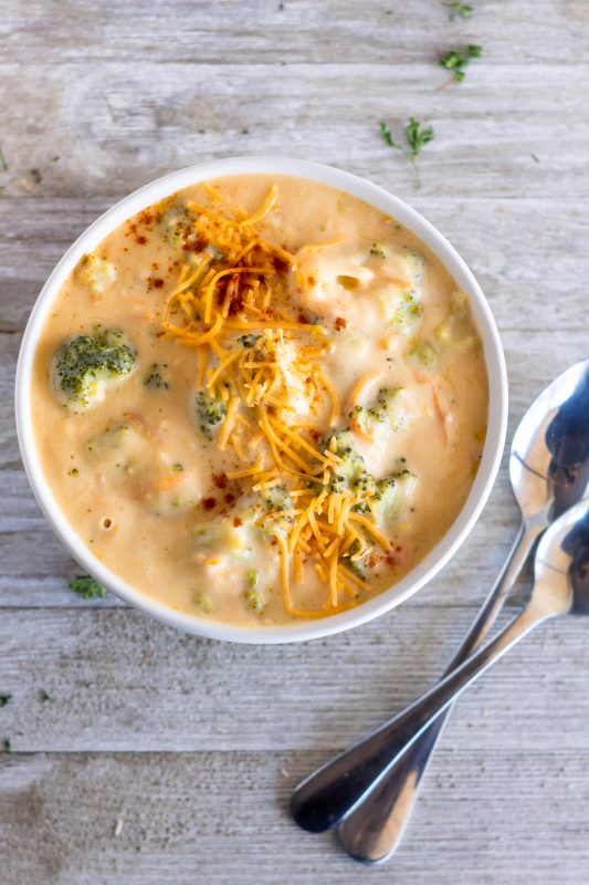 Overhead shot of broccoli cheddar soup garnished with cheese and cayenne pepper on Sweet Tea and Thyme | www.sweetteaandthyme.com