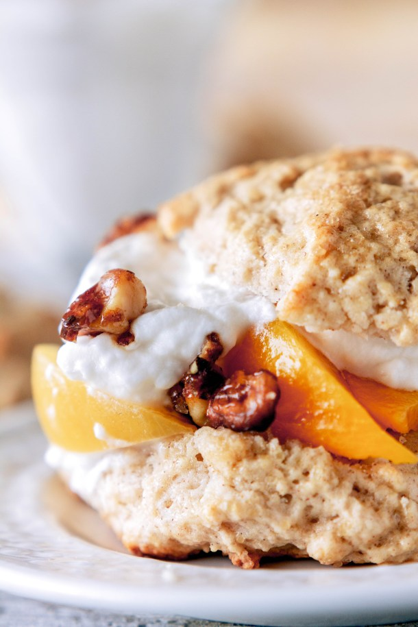 Spiced peach shortcake biscuits sop up sweet peach juice and are topped with a hearty dollop of whipped cream and candied nuts.