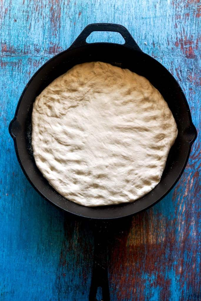 the pizza dough in the cast iron pan has been pressed to the edges