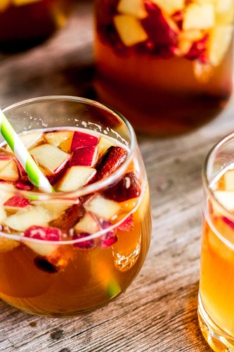 Close up of apple sangria recipe in wine glass with cinnamon stick and fruit