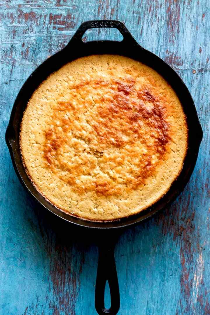 overhead shot of cast iron cornbread in skillet on a blue painted wood board