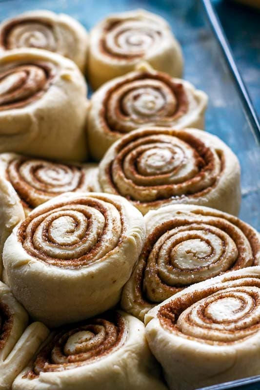 a closer view of the best cinnamon rolls risen in their baking pan