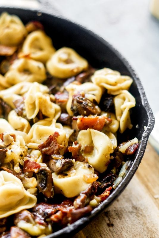 a close up of tortellini, bacon and mushrooms mixed in a cast iron pan