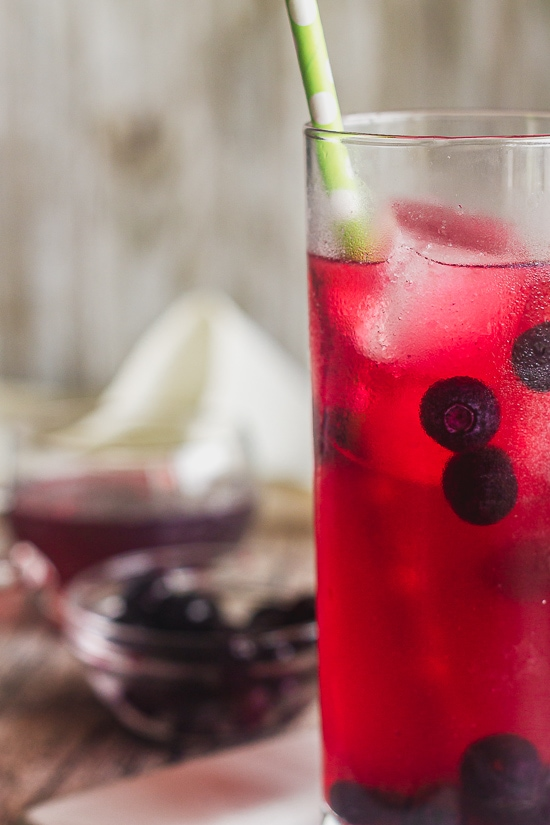 a close up of a glass of moscow mule flavored with blueberry simple syrup. There are frozen blueberries in the glass.