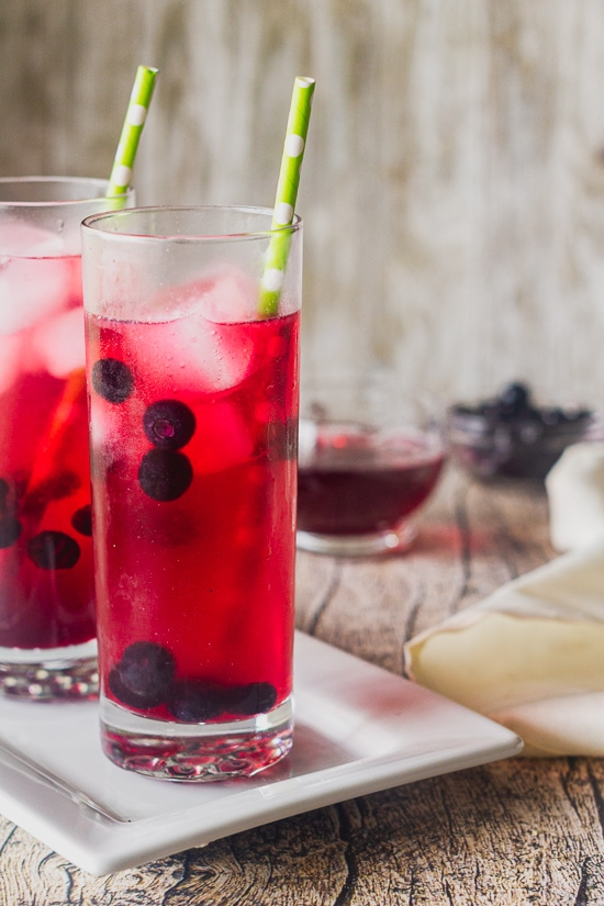 two highball glasses filled with blueberry moscow mule cocktails on a rectangle platter with blueberries and simple syrup sitting behind the glasses.