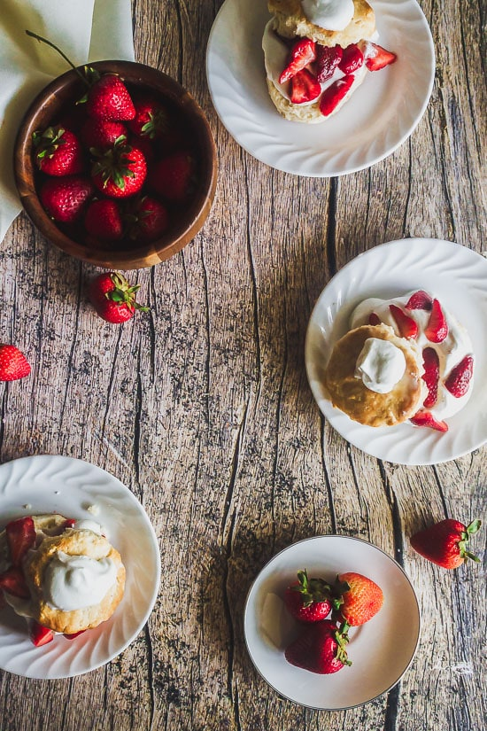 overhead shot of homemade strawberry shortcakes on plates with a bowl of strawberries and strawberries strewn about on a wooden table