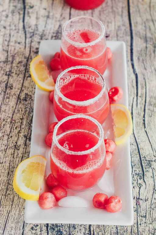 three glasses of watermelon agua fresca on a long rectangular platter with melon balls and ice