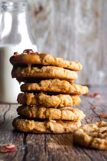 stack of praline cookies with a glass of milk