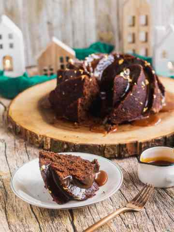a slice of chocolate mayo cake sits on a plate in front of the platter holding the cake