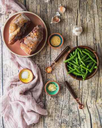overhead shot of the ingredients in slow cooked southern green beans. A bowl of snapped green beans, a plate of thawing ham hocks, garlic, onion powder, and salt