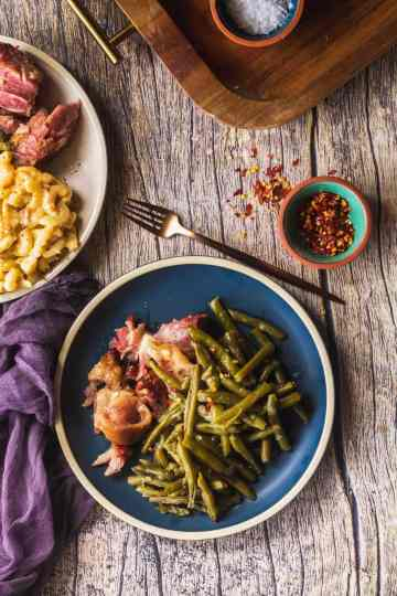 a blue plate full of soul food green beans with ham hock