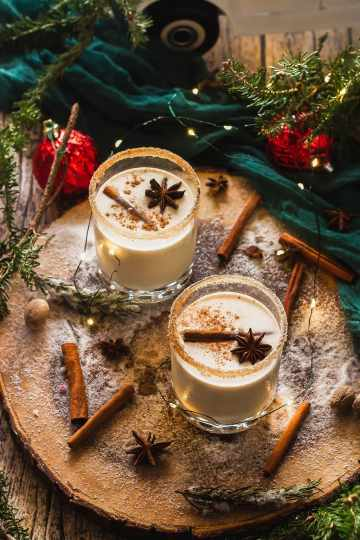 coquito sitting on a rustic wood serving platter with fresh christmas tree branches, cinnamon sticks, anise seeds, nutmeg, holiday lights, and ornaments