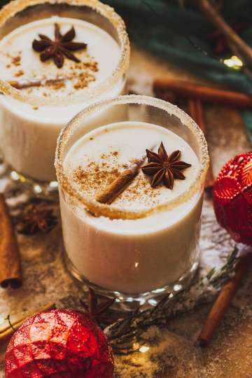 close up of a cinnamon-sugar rimmed glass of authentic puerto rican coquito, garnished with nutmeg and cinnamon, sitting with holiday ornaments