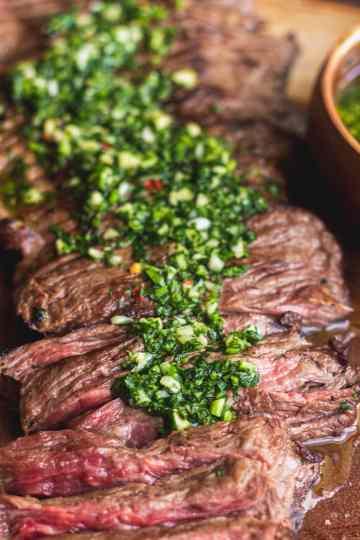 a close up of chimichurri sauce poured over churrasco skirt steak