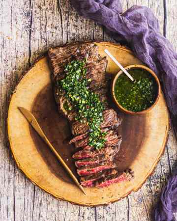 overhead shot of marinated grilled skirt steak with chimichurri sauce on a wooden board