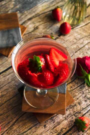 a love martini valentine's day cocktail made with rum and peach schnapps garnished with sliced strawberries