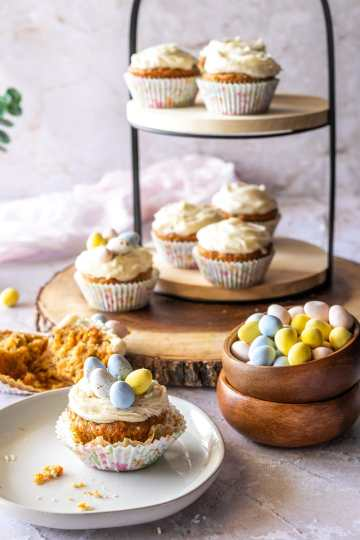 a tray and plate with decorated and undecorated carrot cake muffins with cream cheese frosting and a bowl of cadbury easter eggs