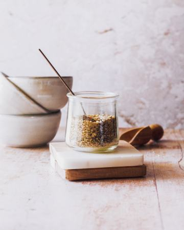 a small jar of homemade lemon pepper seasoning blend sits on marble coasters with a spice shovel