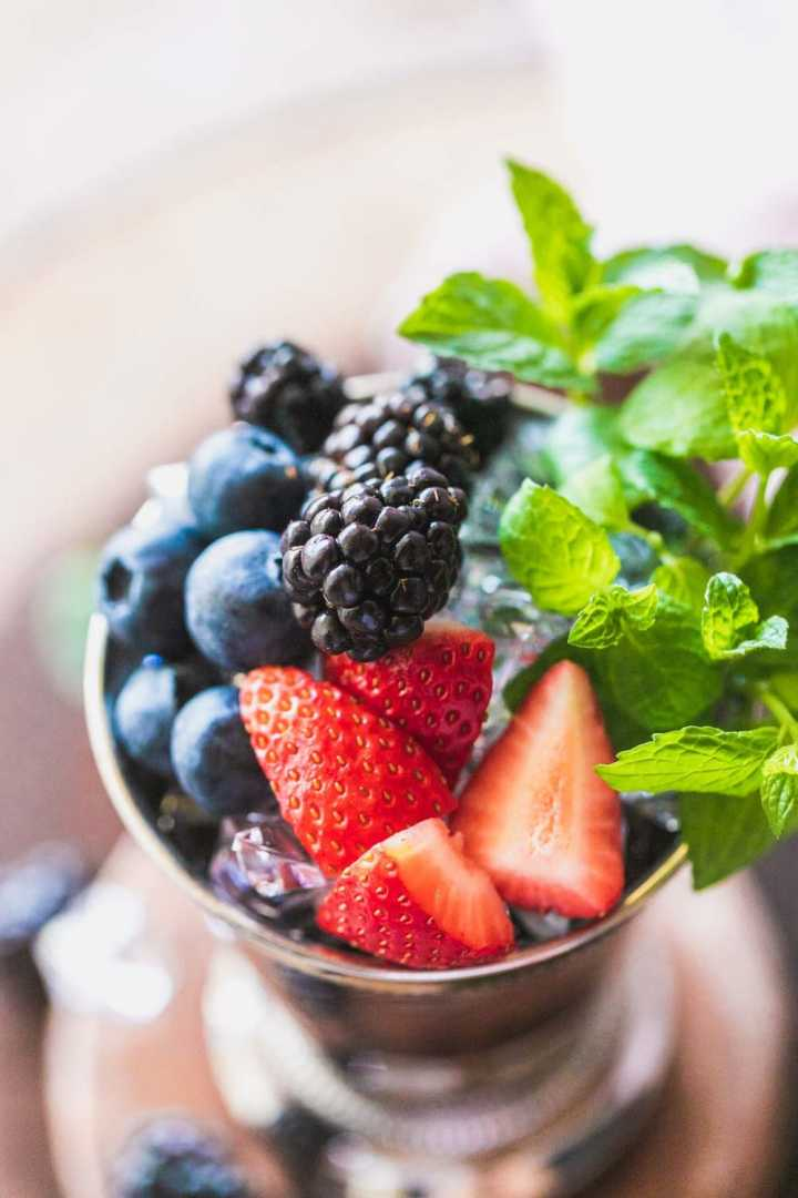 close up view of blackberries, mint sprigs, and strawberries on top of a mint julep