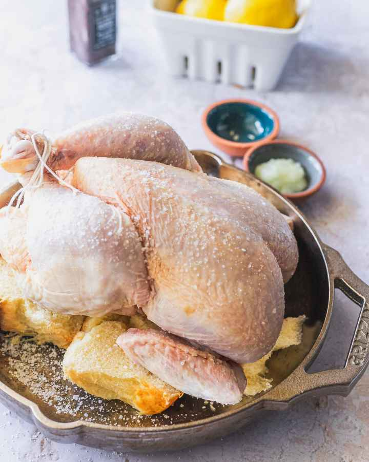 seasoned raw whole chicken on top of sourdough bread in a cast iron pan