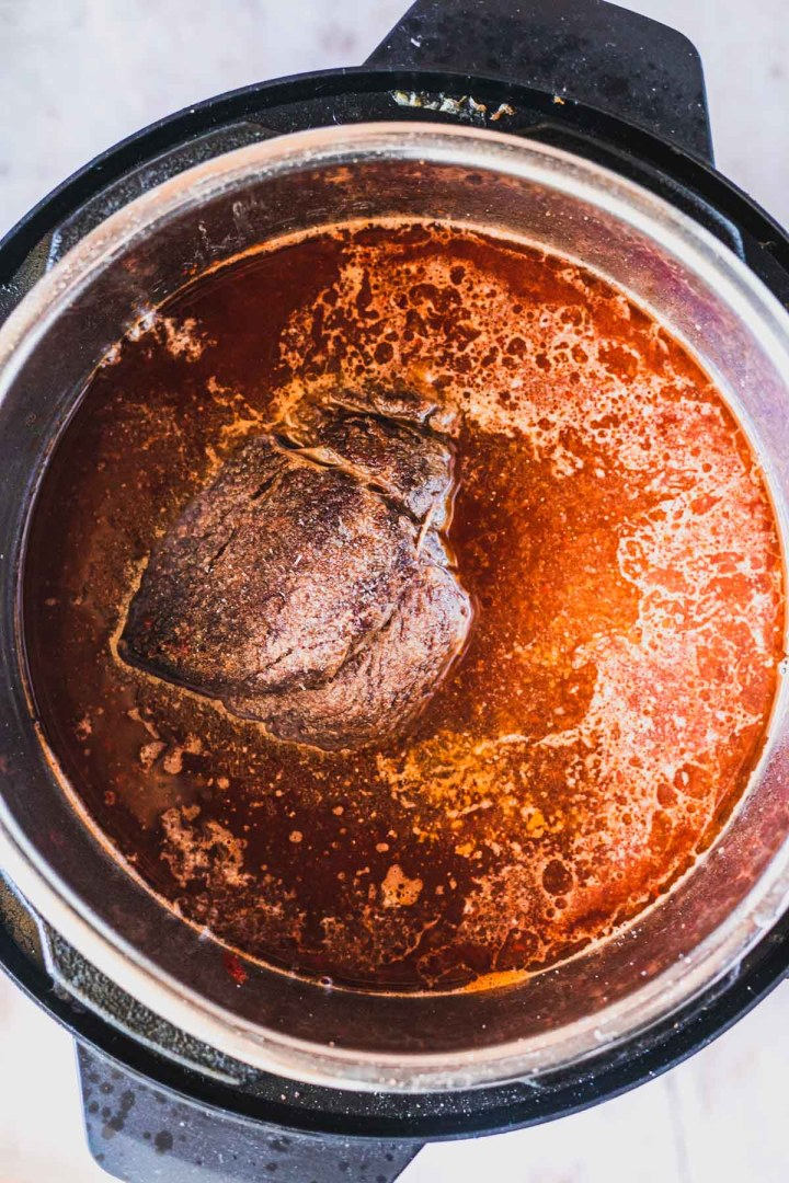 beef in the instant pot with beef broth, apple cider vinegar, and birria sauce before pressure cooking
