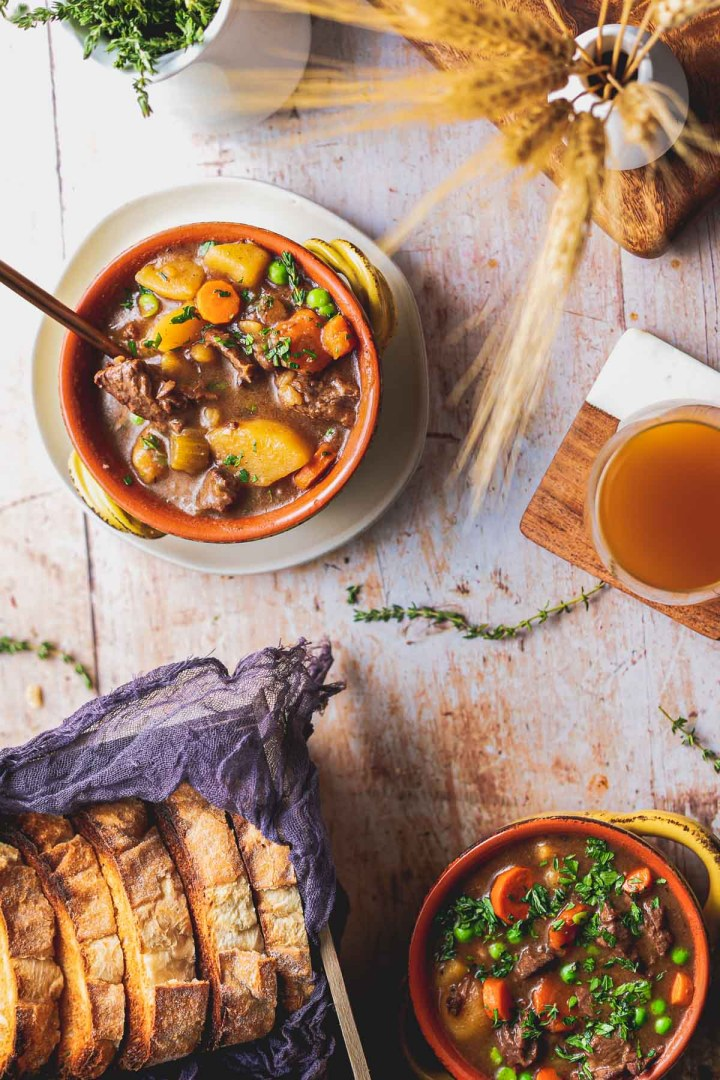 overhead shot of two bowls of beef stew with herbs and toasted bread