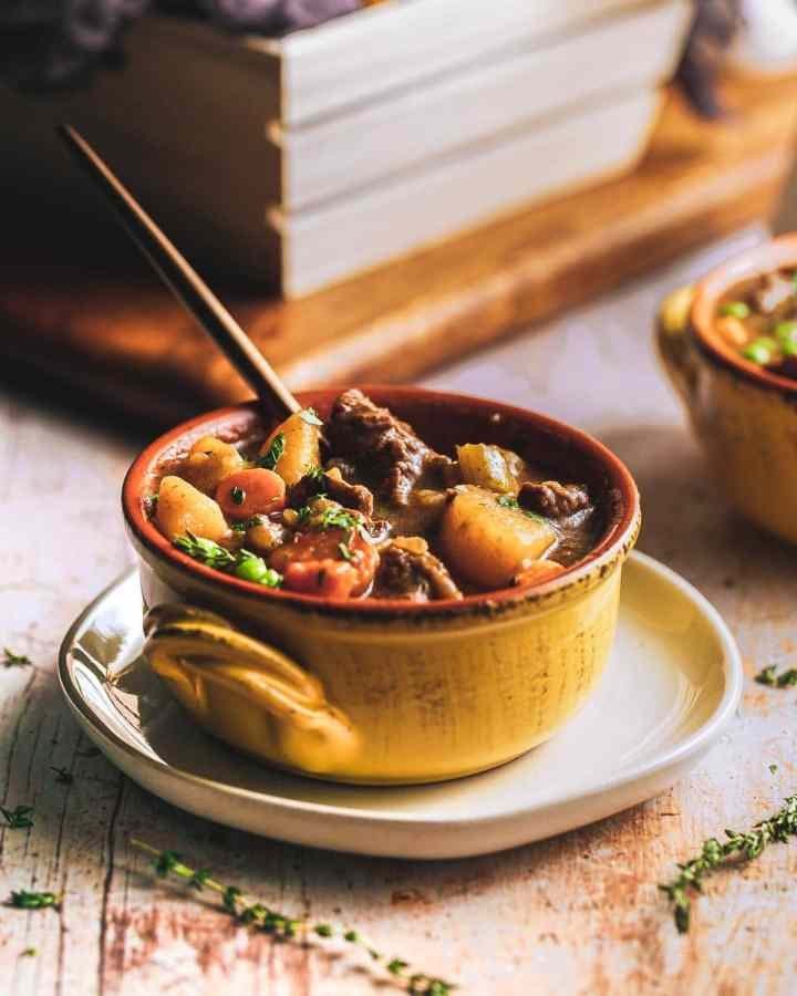 homemade beef stew with thyme being served on a plate