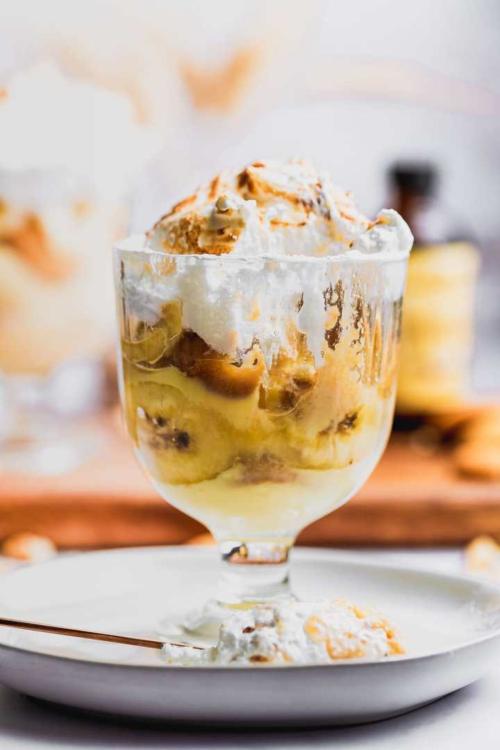 a spoonful of african american banana pudding sitting on a plate with a small trifle bowl filled with the dessert