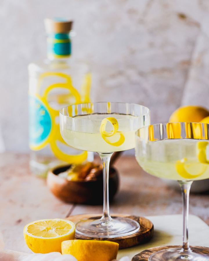 two coupe glasses of bees knees cocktails in front of a bottle of limoncello gin, lemons, and honey