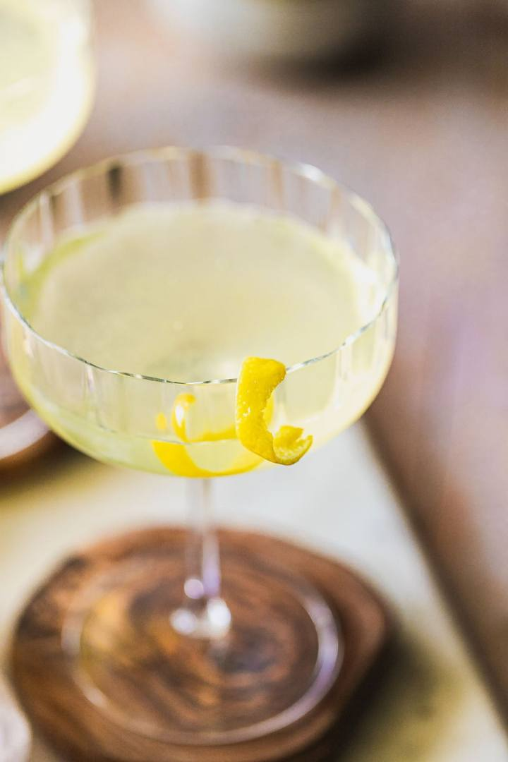 close up look at a lemon twist garnish on a bees knees cocktail coupe glass