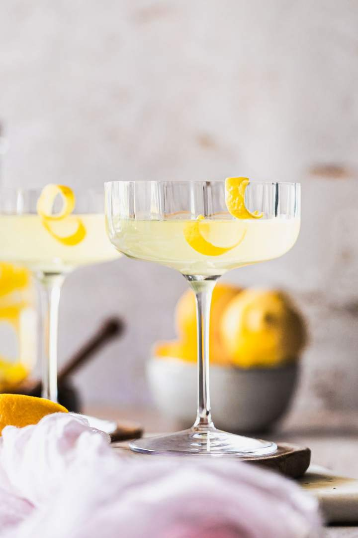 a tall stem coupe glass with prohibition era bee's knees drink and a lemon twist