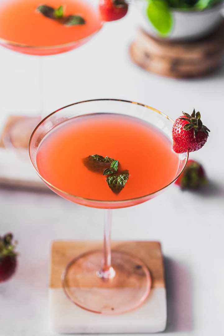 a close view of flamingo drink in gilded rim coupe garnished with mint
