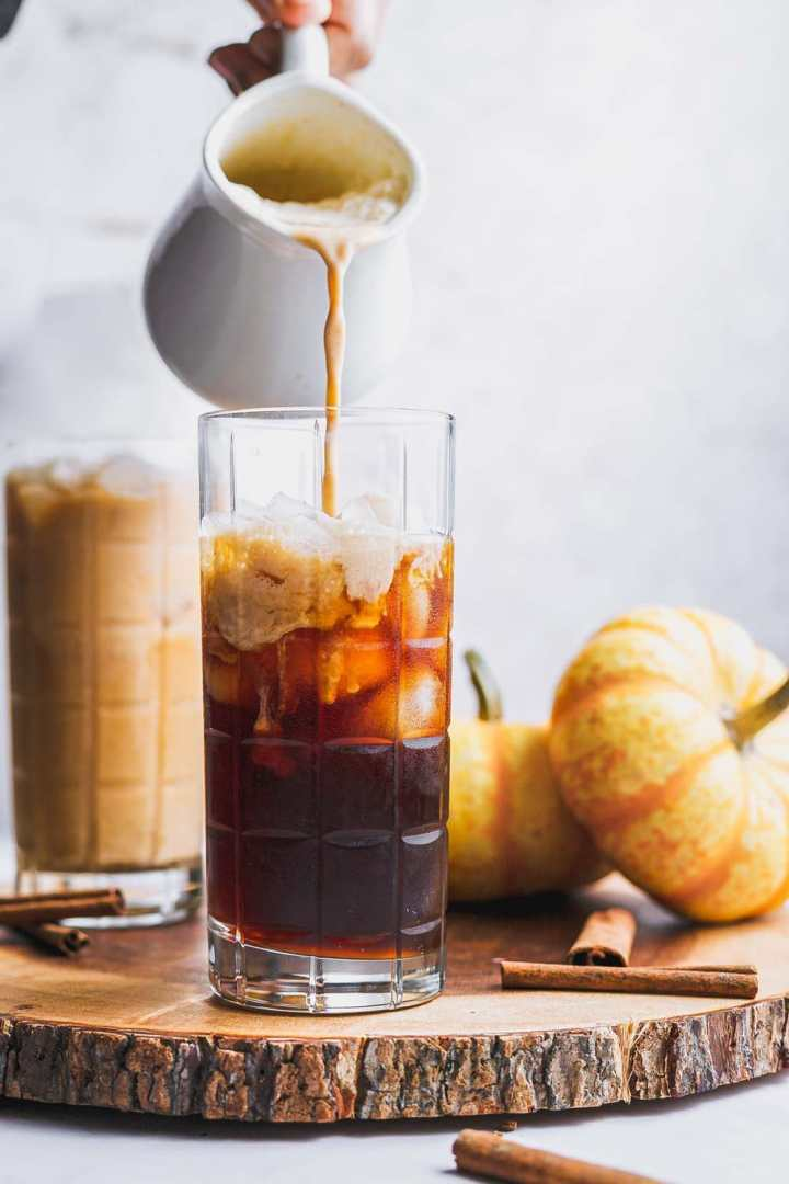 a glass of cold brew coffee before the pumpkin cream cold foam is poured in