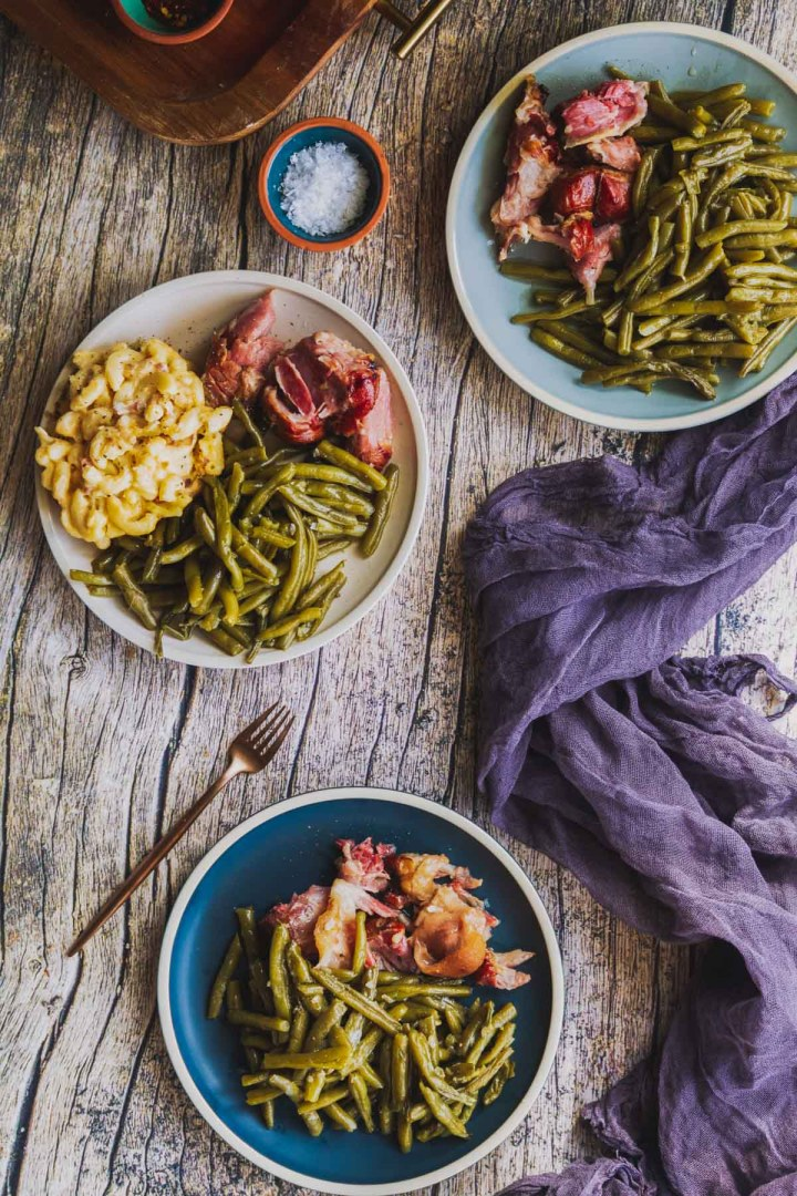 overhead shot of three plates of slow cooked southern green beans served with ham hock and baked macaroni and cheese