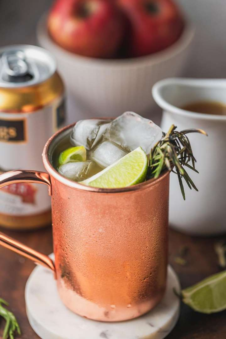 view of ginger beer, apple cider, and limes with a copper cup filled with sweet apple cider moscow mule