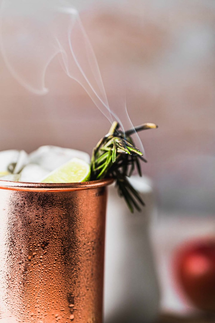 a close up of the smoking rosemary sprig garnish peeking out of a copper mug full of apple cider mule