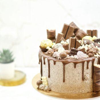 Chocolade Drip Taart met verschillende stukken chocolade erop
