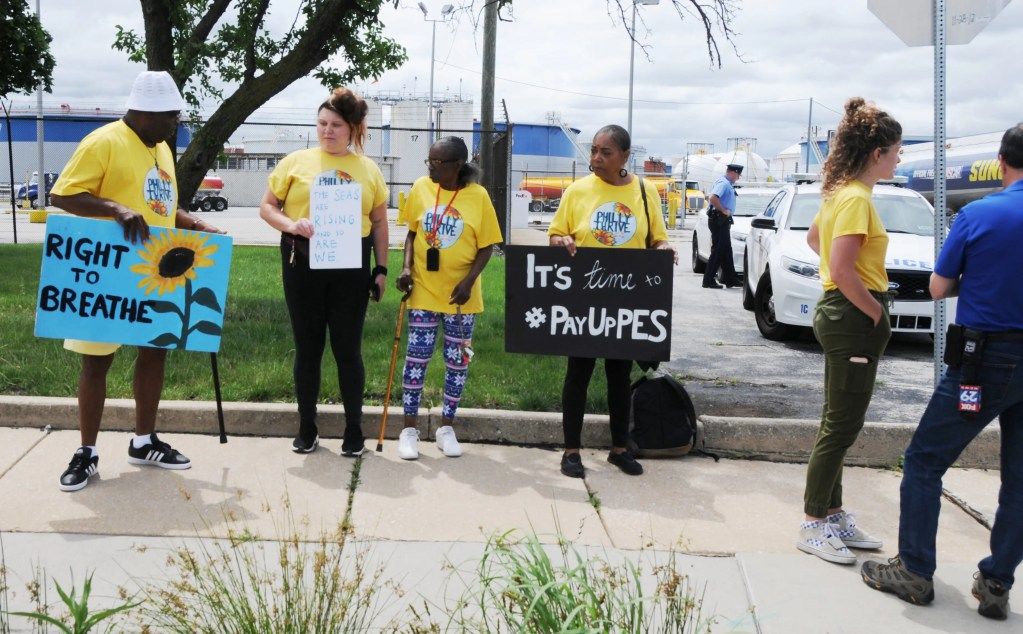 "Photo:  South Philly activist Sylvia Bennett of  Philly Thrive (center) protests outside the entrance to the Phila. Energy  Solutions Plant on Passayunk Avenue after the massive explosions there on the  morning of June 21.  ""It was 'boom,  boom, boom' and I was rocked out of my bed!"" she said.  Philly Thrive spokesperson Alexa Ross  (right) gets the message across to a TV10 reporter."