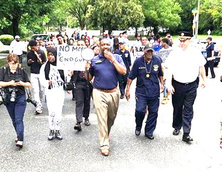 """City Councilman Kenyatta Johnson (center, with bull horn) leads a walk down Southwest streets with disconsolate community members, many of them former West Africans, after the Fathers' Day shootings.   Between Councilman Johnson and 12th Police District Captain Scott Drissel is Pastor and activist Paul """"Earthquake"""" Moore."""