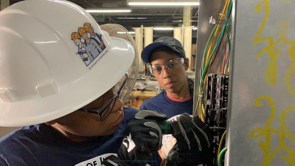 Dana Pinkney and Asia Wilkerson working on commercial electrical panel 3-phase