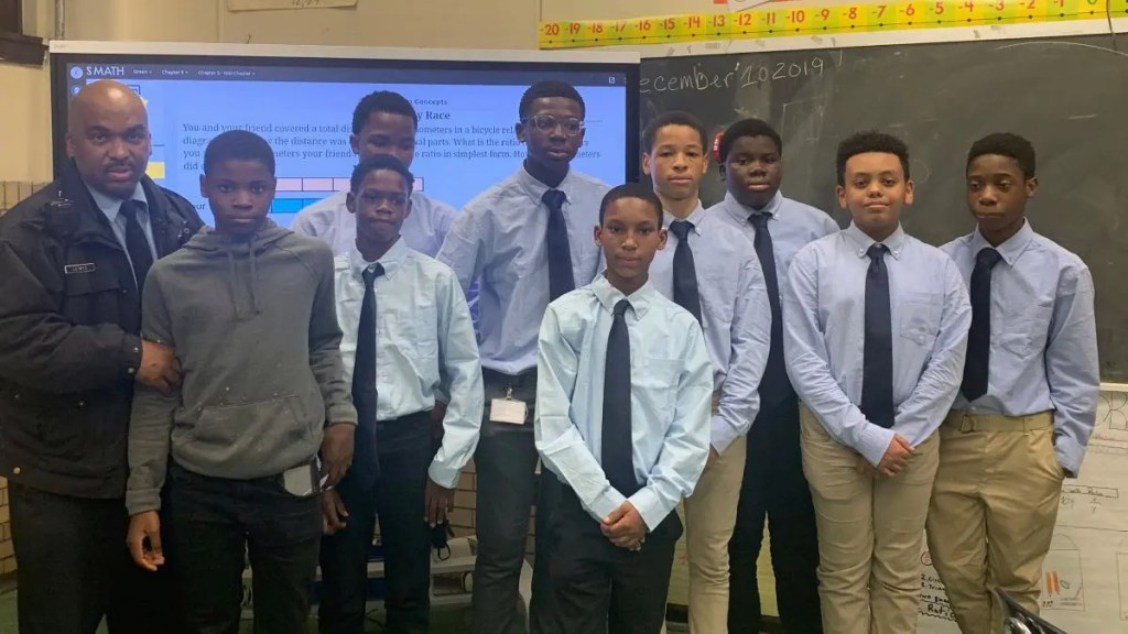 Philadelphia School District Officer Donald Lewis and the group of young men he is mentoring at Tilden Middle School in Southwest.